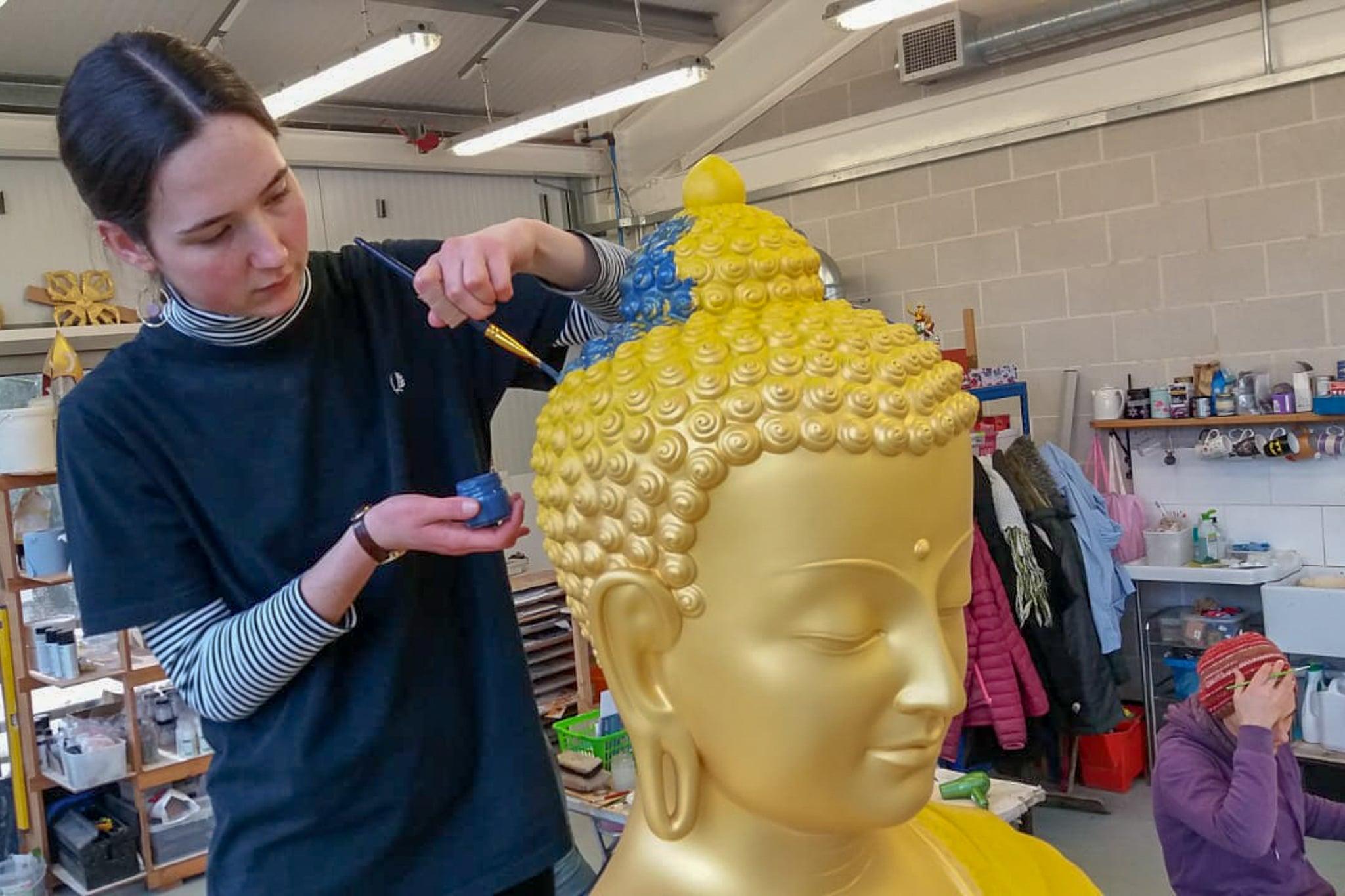 Voluntario trabajando en una estatua de Buda en el Estudio de Arte Kadampa