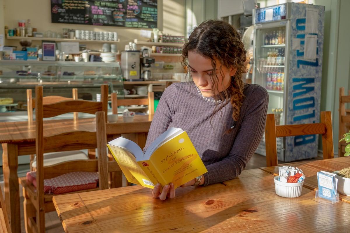 Moça lendo o Caminho Alegre da Boa Fortuna